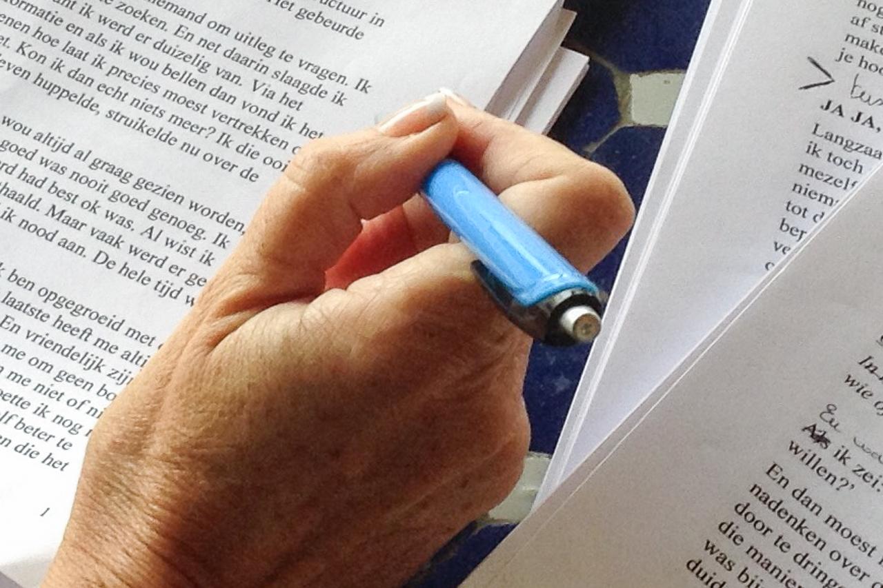 Een hand met azzurblauwe pen corrigeert tekst